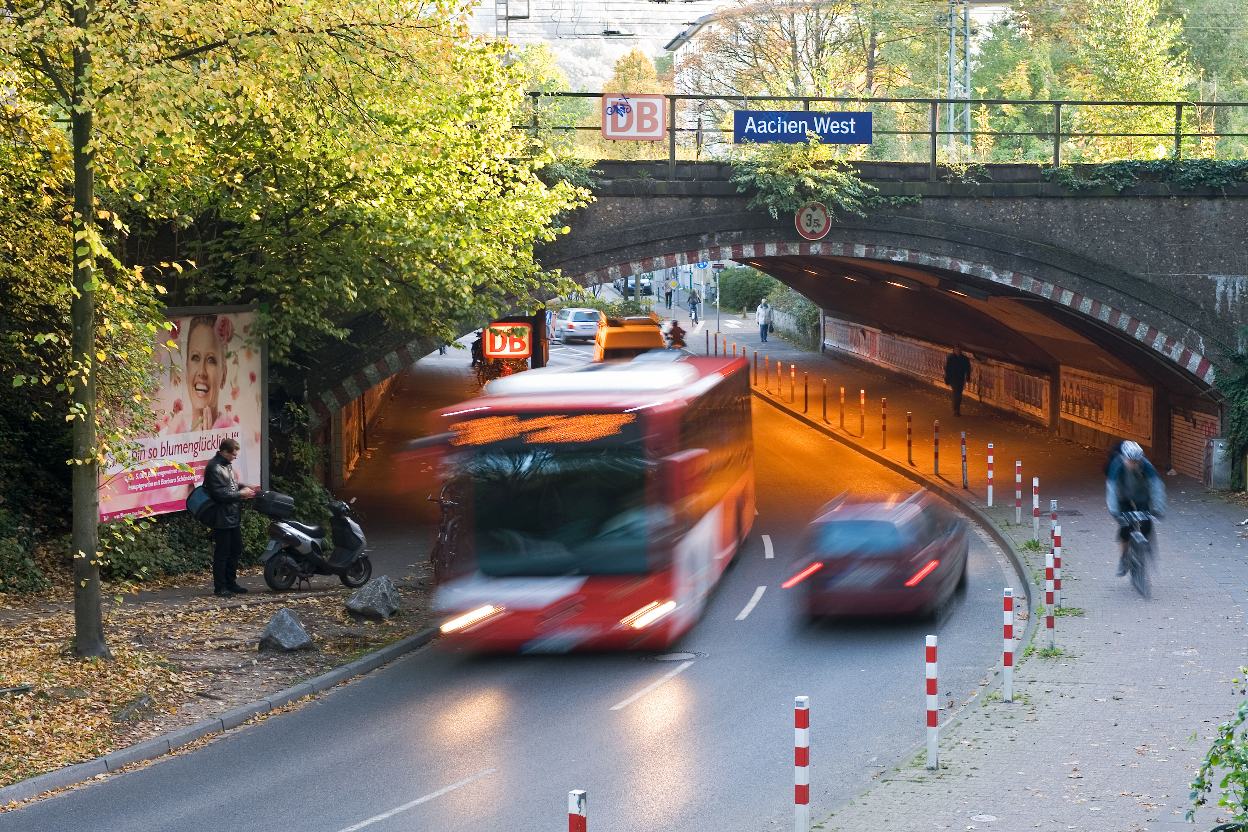 A bus crosses a through the railway bridge in Aachen West in the evening sun.